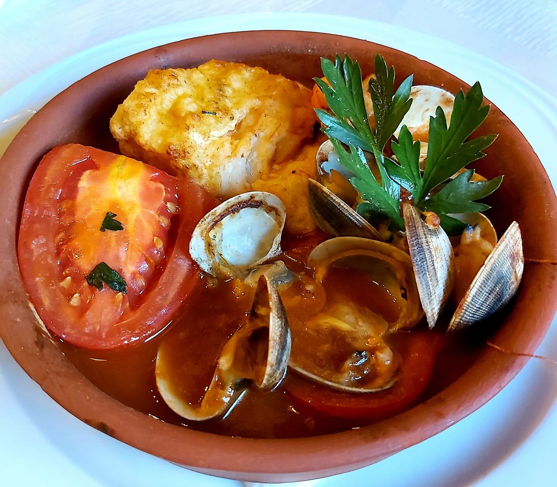 RESTAURANT RECOMANAT RESTAURANT CAN BENET Suquet de bacallà fresc amb cloïsses fresques de Galícia. Amanida tèbia de gambes